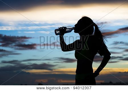 young woman Runner drinks water after training