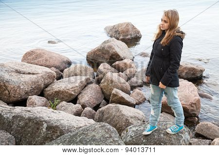 Caucasian Teenage Girl Walking On Coastal Stones