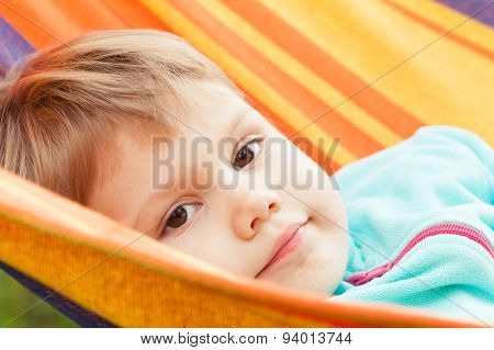 Cute Blond Baby Girl Lying In Striped Hammock