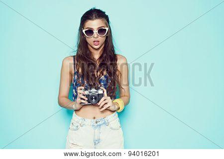 fashion stylish woman sungalasses making photo using retro camera. Portrait on blue background in wh