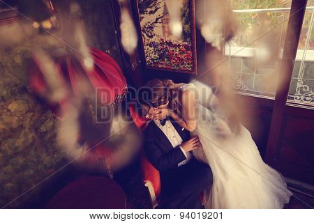 Bride And Groom Sitting On Chair In A Beautiful Room