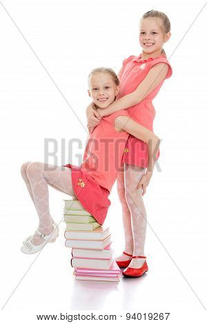 Charming sisters frolic sitting on a stack of books