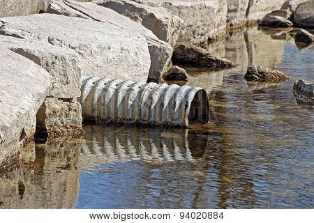 Large metal drain pipe leading out into natural lake