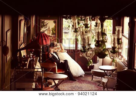 Bride And Groom Sitting On A Chair In A Beatufiul Room