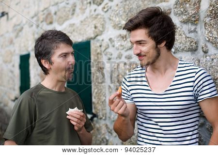 two friends having a snack and talking outdoors