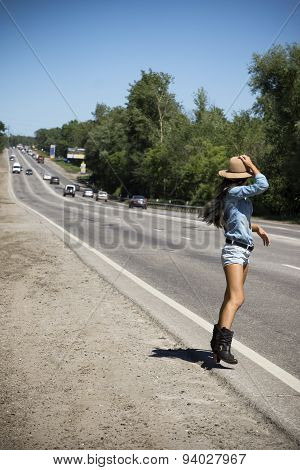 Young Beautiful Woman Hitchhiking Along A Road