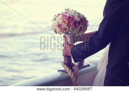 Hands Of A Bride Holding Wedding Bouquet With Her Groom On Boat