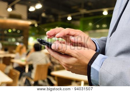 Business Man Using Mobile Smart Phone In Restaurant Or Food Court Plaza