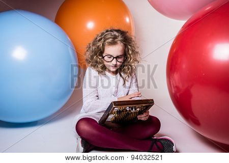 Thoughtful Curly Teen Girl In Glasses With Wooden Abacus On The Background Of Large Rubber Balls