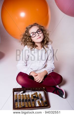 Teen Girl In Glasses With Wooden Abacus On The Background Of Large Rubber Balls.