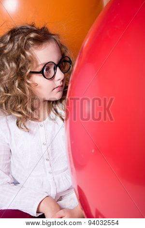Beautiful, Smart Curly Teen Girl In Glasses On The Background Of Large Rubber Balls.