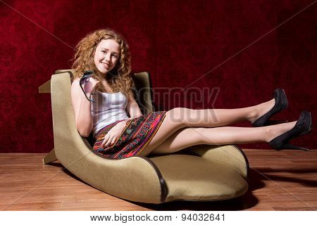 Cheerful Young Girl Sitting On A Chair Fashion On A Red Background
