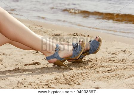 Woman feet in sandals on the beach