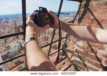 Tourist makes a travel photo from the top of Asinelli tower in Bologna, Italy.