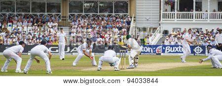 NOTTINGHAM, ENGLAND - July 13, 2013: Graeme Swann bowls the ball to Ed Cowan as the fielders crowd around during day four of the first Investec Ashes Test match at Trent Bridge Cricket Ground