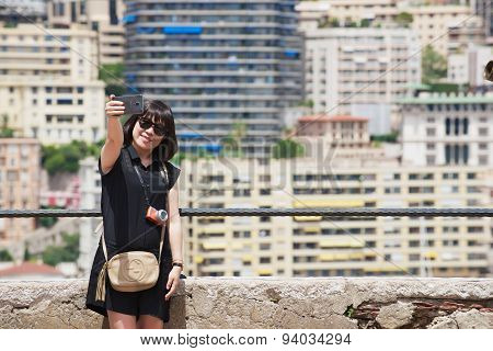 Asian lady makes selfie with a smartphone at the viewpoint in Monaco.