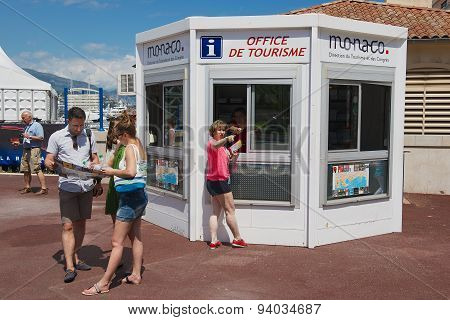 People get maps and directions at the office of tourism booth in Monaco.