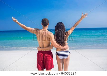 Rear view of happy couple with arms outstretched at the beach on a sunny day