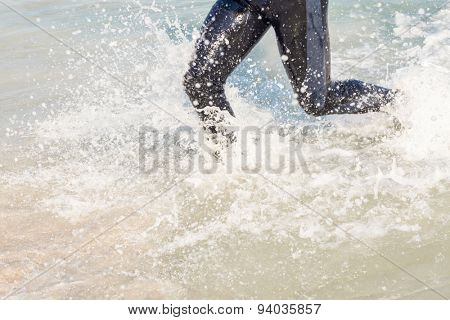 Swimmer running in the ocean on a sunny day