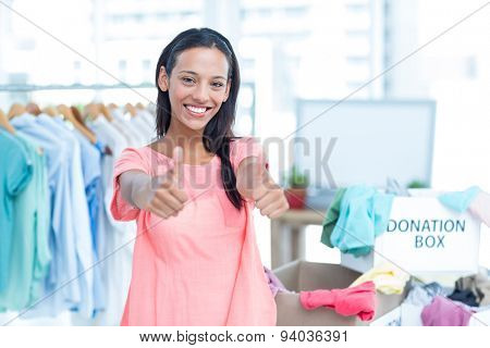 Portrait of a smiling young female volunteer gesturing thumbs up