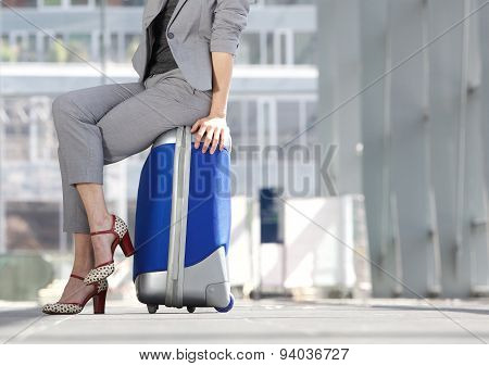 Business Woman Sitting On Suitcase At Airport