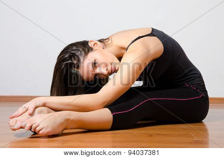 Beautiful Young Ballerina Stretching On The Floor During Training