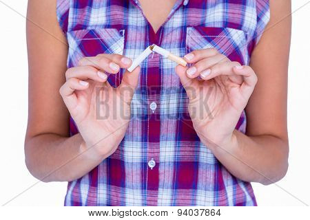 Hands of woman snapping cigarette on white background