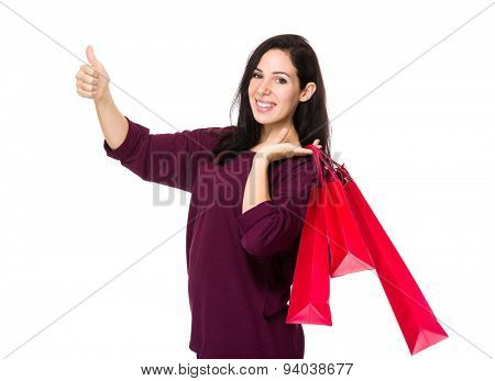 Brunette woman hold with shopping bag and thumb up