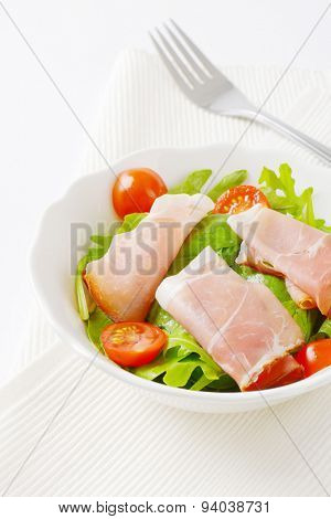 bowl of dried pork ham, rucola and spinach leaves and halved cherry tomatoes on white place mat
