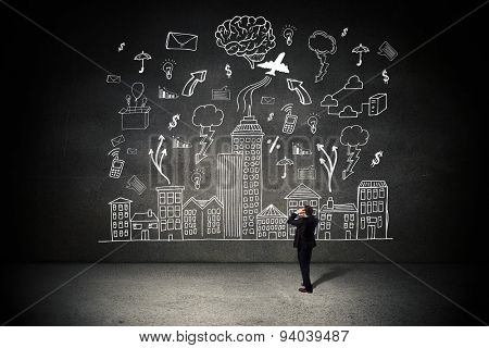 Stressed businessman with hands on head against black wall