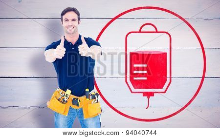 Man wearing tool belt while showing thumbs up sign against painted blue wooden planks