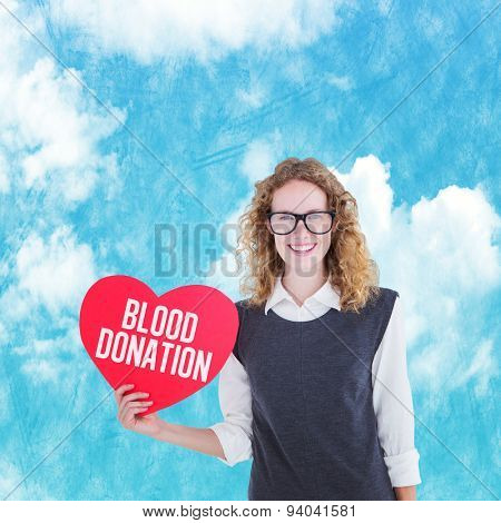 Geeky hipster holding heart card against painted blue sky