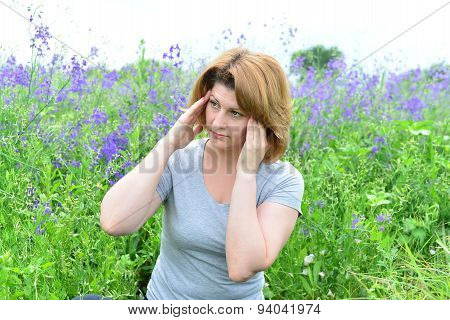Adult Woman With A Headache On The Meadow