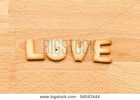 Word Love biscuit over the wooden background