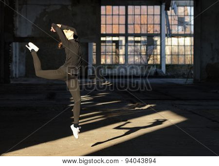 Young Modern Dancer Jumping High In The Air In Abandoned Building