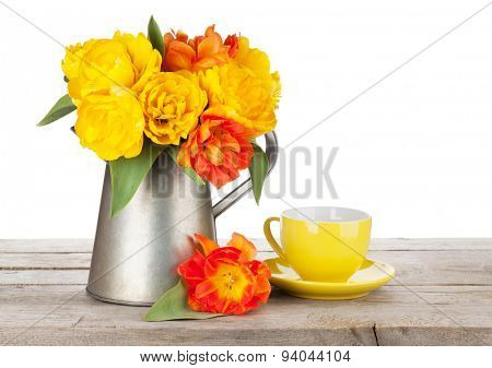 Colorful tulips bouquet in watering can and coffee cup on wooden table. Isolated on white background