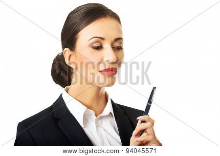 Portrait of thoughtful businesswoman holding a pen.