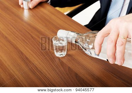 Closeup on male hand pouring vodka into a glass.