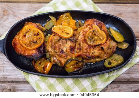 Delicious Baked Chicken Thighs With Lemon Slices, Onion And Zucchini Served In Cast-iron Frying Pan