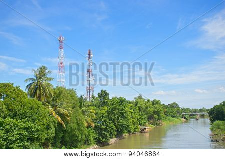 Antenna Cellular Tower In Forest Beside River And Blue Sky