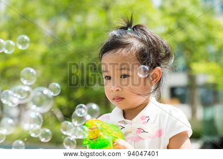 Lovely Girl play with bubble blower at outdoor