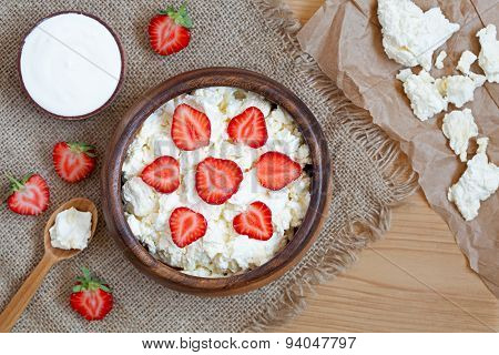 Healthy homemade cottage cheese breakfast or lunch with strawberry, sour cream and nuts in wooden di