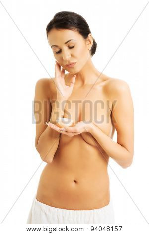 Portrait of a topless woman with cream container.