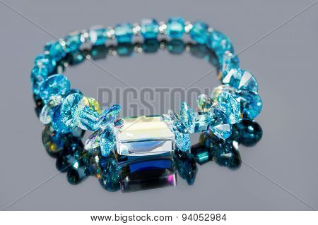 beautiful blue bracelet on gray background.