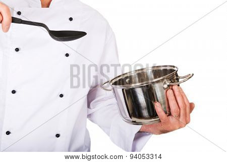Restaurant chef's hand holding steel pot and spoon