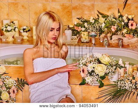 Blonde woman relaxing at flower water spa.