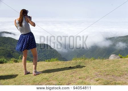 Young brunette girl taking photos of the mountain scenery, Madeira, Portugal