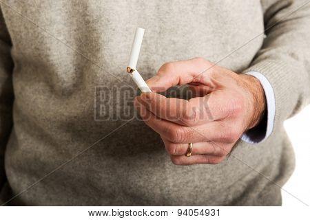 Mature male hand with broken cigarette.