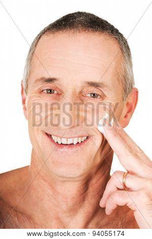 Mature man applying cream on his face.