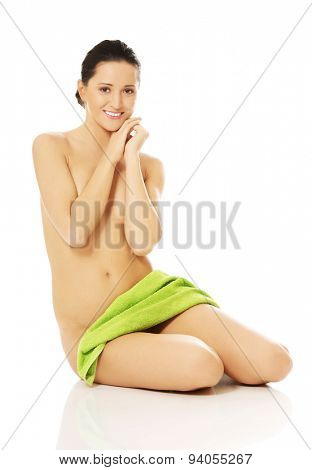 Front view of nude woman sitting, touching chin and wrapped in towel.